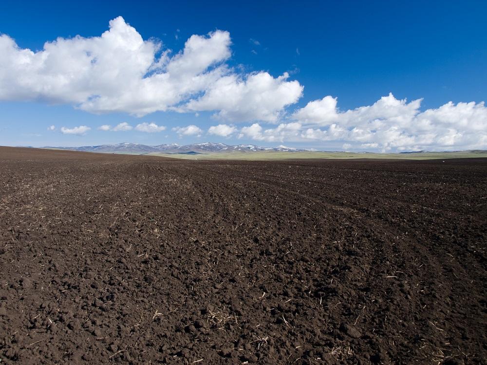 Terreno bajo cielo azul con nubes